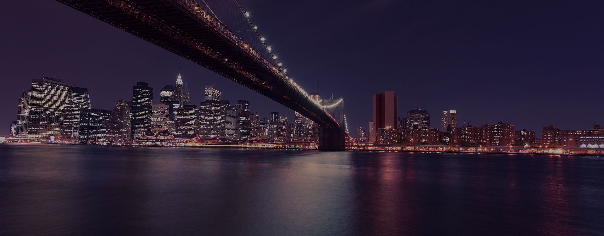 Skyline of NYC and the Brooklyn Bridge at night.
